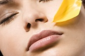 Young woman's face with flower petal (close-up)