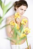 Junge Frau mit gelben Orchideenblüten