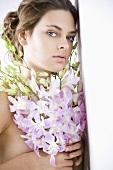 Junge Frau mit Strauss aus Orchideen