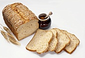 Sliced Loaf of Whole Wheat Bread with Honey Jar