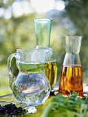 Water in glass jug, oil and vinegar in carafes