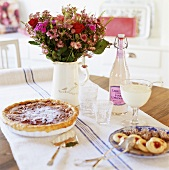 Tart, small cakes, lemonade and jug of flowers on table