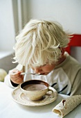 Little boy drinking cup of cocoa with spoon