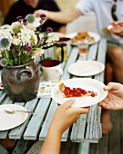 Friends having coffee and cakes at garden table