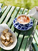 Tea with milk and biscotti on garden table