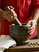 Person grinding spices in a mortar