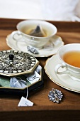 Cups of tea and tea bags on tray