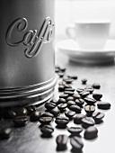 Coffee beans beside coffee tin
