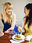 Two girl friends talking while eating