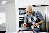 A man laughing while cooking