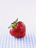 A strawberry on checked fabric