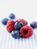 Raspberries and blueberries on checked fabric