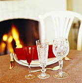 Place-setting and crystal glasses on table in front of fire