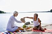 Zwei Frauen beim Picknick am See