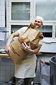 Baker holding sack of flour
