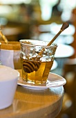 A glass of honey with honey dipper