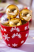 Gold Christmas baubles in two bowls