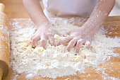 Child's hands kneading dough