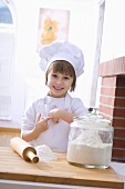 Kleines Mädchen mit Kochhaube, Mehl und Nudelholz