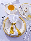 Place-setting with cup of tea, wine and meringue