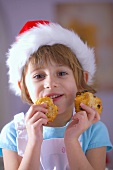 Little girl in Santa hat eating raisin biscuits