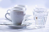 Three cups of espresso with glasses of water