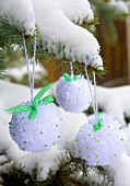 Snowball pompoms hanging on a snow-covered fir branch