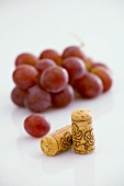 Two wine corks with red grapes
