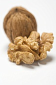 Shelled walnut in front of unshelled walnut