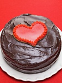 Chocolate cake with red heart-shaped biscuit