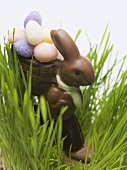 Chocolate Easter Bunny with sugar eggs in grass