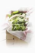 Fresh mangetout on tea towel in woodchip basket