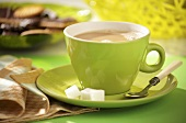 Milky coffee in green cup and saucer