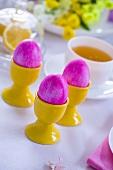 Pink Easter eggs in eggcups, cup of tea behind
