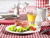 A table laid for breakfast with open ham sandwiches, eggs and orange juice