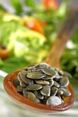 Pumpkin seeds on a spoon in from of a bowl of salad