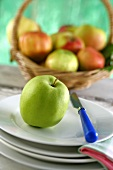 An apple on plate in front of a basket of fruit