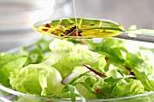 Vinaigrette on a spoon above a bowl of salad