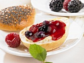 A bread roll spread with butter and berry jam