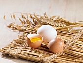 A cracked open egg and ears of wheat on a straw mat