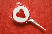 Lollipop with heart on red background