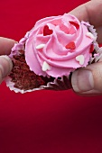 Taking chocolate cupcake with pink icing out of paper case