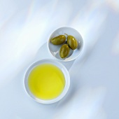 Olive oil and green olives in small dishes (overhead view)