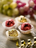 Four chocolates with wine jelly filling in shiny foil
