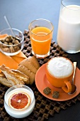 Italian breakfast: juice, cappuccino, yoghurt and biscuits