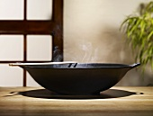 Steaming wok on wooden table