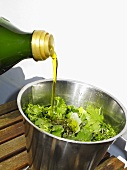 Pouring olive oil over herbs (ingredients for pesto)
