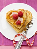 Heart-shaped pancakes with raspberries and maple syrup