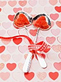 Red sugar hearts in silver spoons with bowl