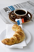 Croissant with French flag, coffee, newspaper
